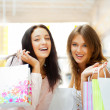 Two excited shopping woman together inside shopping mall. Horizo - Stock Photo