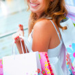 Stock Photo: Happy shopping womat mall preparing gifts for her friends