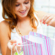 Photo of young joyful woman with shopping bags on the background — Stock Photo #6569099
