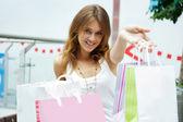 Foto di giovane donna gioiosa con borse della spesa sullo sfondo — Foto Stock