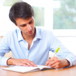 Businessman sitting indoors and writing plan in his diary — Stock Photo