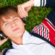 Student outside laying on grass and listening music school. Phot — ストック写真