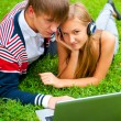 Royalty-Free Stock Photo: Happy young couple using laptop while lying on grass