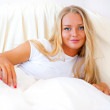 Young blond woman enjoying a sunny morning in bed — Stock Photo #6580406