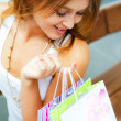 图库照片: Happy shopping woman with bags and smiling. She is shopping insi