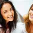 Two women whispering and smiling while shopping inside mall — Stock Photo