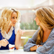 Two beautiful women drinking coffee and chatting at mall cafe. — Stock Photo #6580525