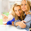 Two beautiful women drinking coffee and chatting at mall cafe. — Stock Photo #6580527