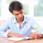 podnikatel sedět uvnitř a psaní plán ve svém deníku — Stock fotografie