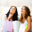 Two excited shopping woman resting on bench at shopping mall. Lo — Stock Photo