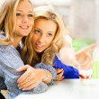Two beautiful women drinking coffee and chatting at mall cafe. - Stock Photo
