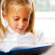 Image of smart child reading interesting book in classroom — Stock Photo