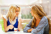 Two beautiful women drinking coffee and chatting at mall cafe. — Stock Photo