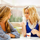 Two beautiful women drinking coffee and chatting at mall cafe. — Стоковое фото