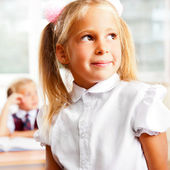 Portrait of a schoolgirl being in a classroom at school with her — Stock Photo