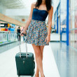 Young pretty stylish woman with luggage at the international air — Foto Stock