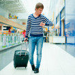 Portrait of a successful young man walking with travel bag at mo — Stock Photo