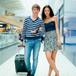 Full-length portrait of young couple in love walking with suitca — Stock Photo #6654719