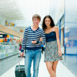 Full-length portrait of young couple in love walking with suitca — Stock Photo #6654724