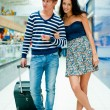 Full-length portrait of young couple in love walking with suitca — Stock Photo