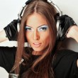 Club style woman with headphones listening to music looking at c — Stockfoto