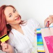 Beautiful shopping woman holding bags and credit card at a mall — Stock Photo