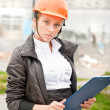 Royalty-Free Stock Photo: Young architect-woman wearing a protective helmet standing on th