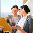 Two business women reading documents — Stock Photo