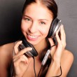 Club style woman with headphones listening to music looking at c — Stock Photo
