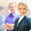 Stock Photo: Portrait of a cute business woman with colleagues at the backgr
