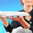 Portrait of young happy woman stewardess holding jet aircraft in — Stock Photo #6654938