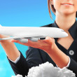 Stock Photo: Portrait of young happy womstewardess holding jet aircraft in