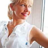 Closeup portret van lachende vrouw permanent in de buurt van grote venster — Stockfoto