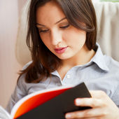 Young sexy woman at home reading book — Stock Photo