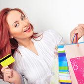 Hermosa mujer compra sosteniendo bolsas y tarjetas de crédito en un centro comercial — Foto de Stock