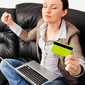 Portrait of a young woman lying on the couch and shopping from t — Stock Photo