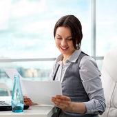 Mulher de negócios bonita olhando papéis ela segurando no seu ar — Fotografia Stock