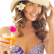 Woman drinking orange juice and wearing summer hat. Vacation con — Stock Photo