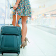 Woman's legs and travel suitcase at modern airport — Stock Photo