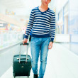 Portrait of young man walking inside modern airport with trolley — Stock Photo #6668588