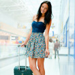 Portrait of young woman walking inside modern international airp — Stok fotoğraf