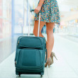 Woman's legs and travel suitcase at modern airport — Stock Photo #6668846