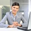 Stock Photo: Young business woman on a laptop at her office