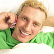 A man in his bed speaking cell phone and looking at camera — Stock Photo #6688235