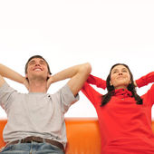 Smiling beautiful couple sitting on a sofa and dreaming about ne — Stock Photo