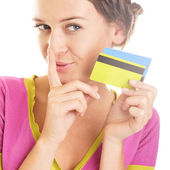 Beautiful young woman looks down at colorful credit cards in her — Stock Photo