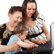 Grandma and Mother with baby with laptop — Stock Photo