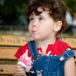 Little girl is eating strawberry ice-cream — Stock Photo