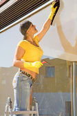 Young woman washing the window — Stock Photo