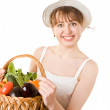 Girl holding a basket of fresh vegetables. - Stock Photo